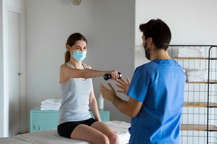 A patient meets with a physiotherapist to recover from a shoulder injury.