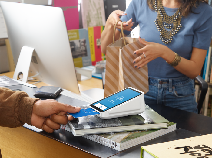A person inserting a credit card into a Square point-of-sale card reader.