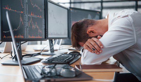 A frustrated investor with their head resting in their arms at their desk, in front of stock charts on computer monitors