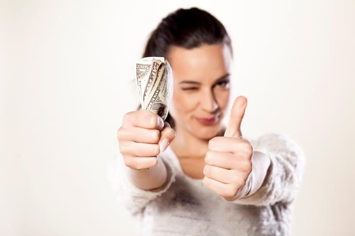 Personne qui donne le pouce en l'air et détient de l'argent.