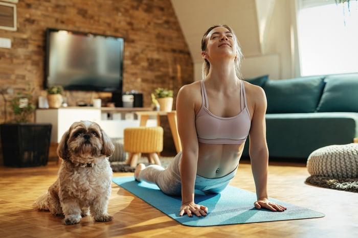Chien assis à côté d'une femme faisant du yoga