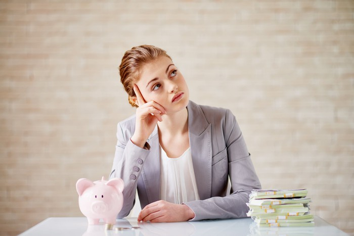 A person sits at a table with a piggy bank and a stack of cash and looks upward in thought.