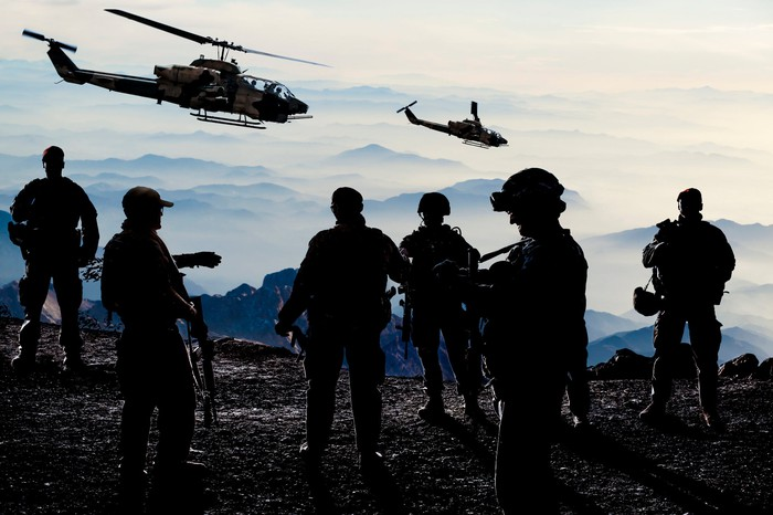 Six soldiers standing together during military training with two helicopters flying overhead.