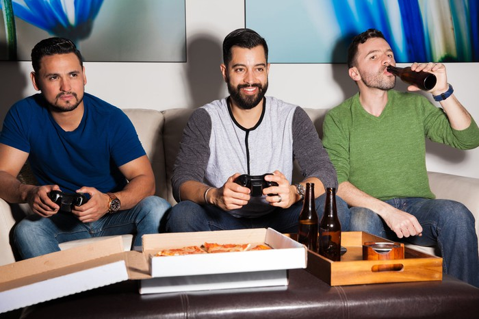 Three people having drinks, eating pizza, and playing video games.
