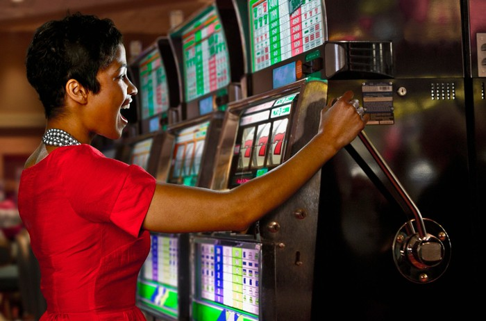 Person pulling handle on slot machine.