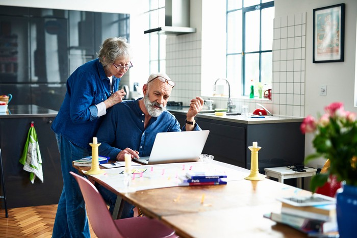 An elderly couple looking at a laptop in their kitchen.