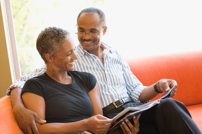 Two smiling people on couch looking at magazine.