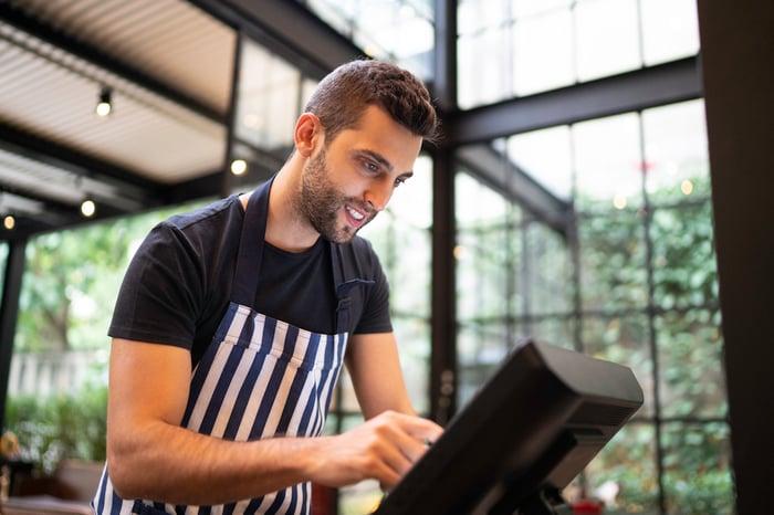 A restaurant employee using a computer terminal.