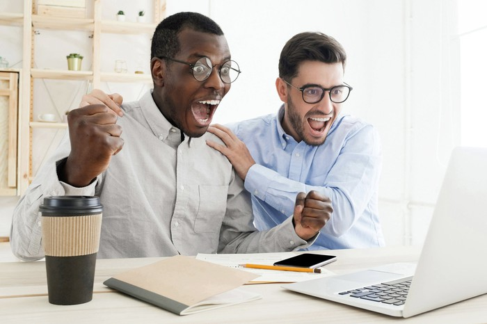 Two persons celebrating as they watch a computer screen.