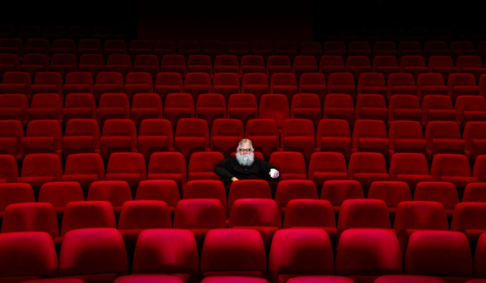 A lone person sitting in an empty movie theater.