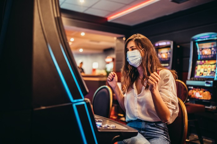 A masked customer plays a slot machine in a casino.