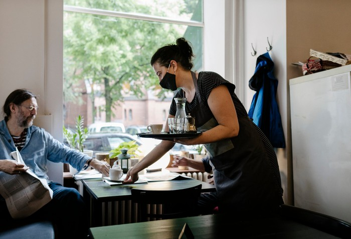 A server delivers coffee to customer at a restaurant.