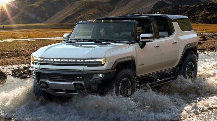 A GMC Hummer EV driving through a shallow pool of water.