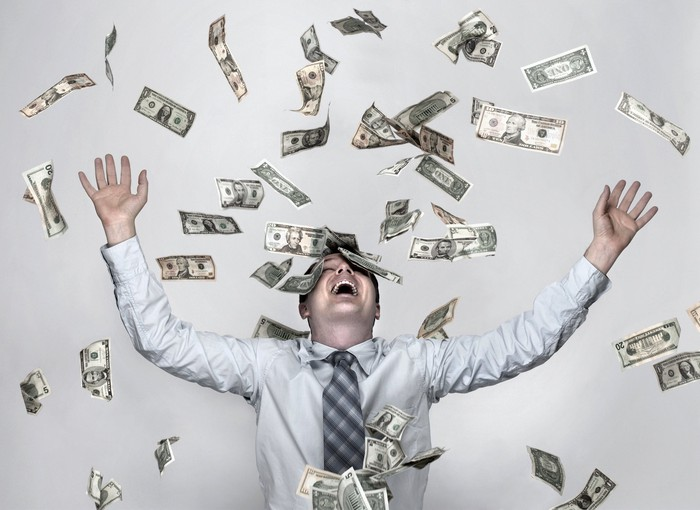 Person with raised hands amid flying money bills.