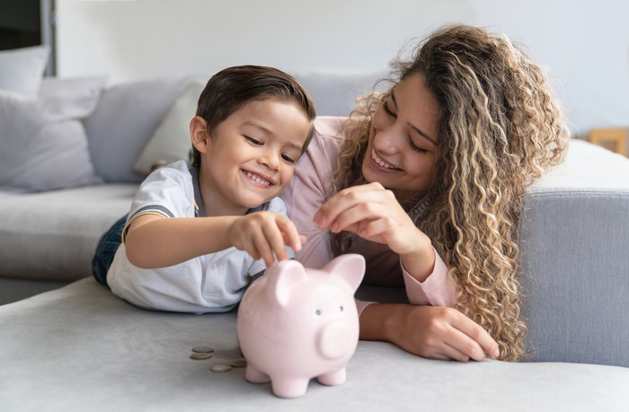 A person and a child putting a coin in a piggy bank.