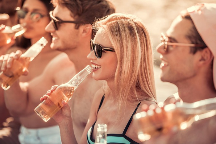 Friends drinking seltzer at beach