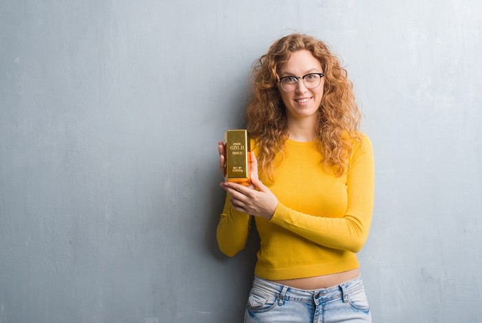 Person holding gold bar.