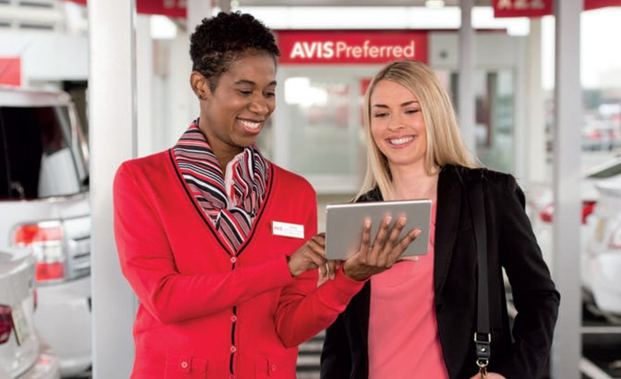 Two people looking at a tablet, with Avis signage and uniform.