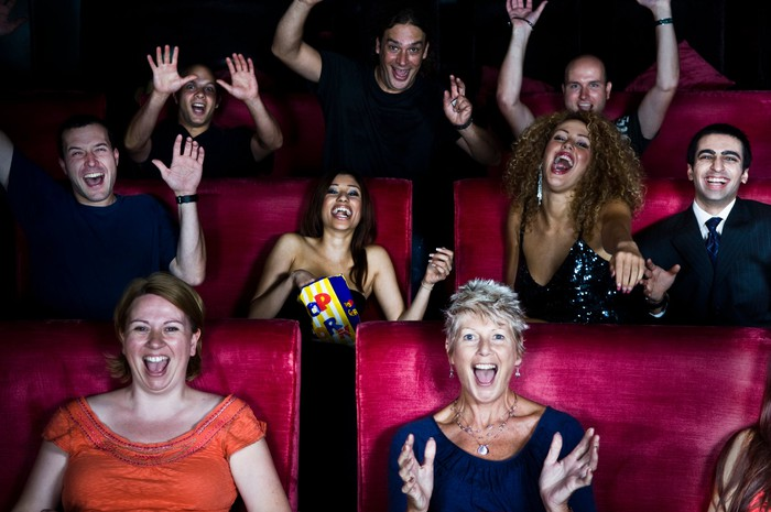 People cheer from their seats in a movie theater.