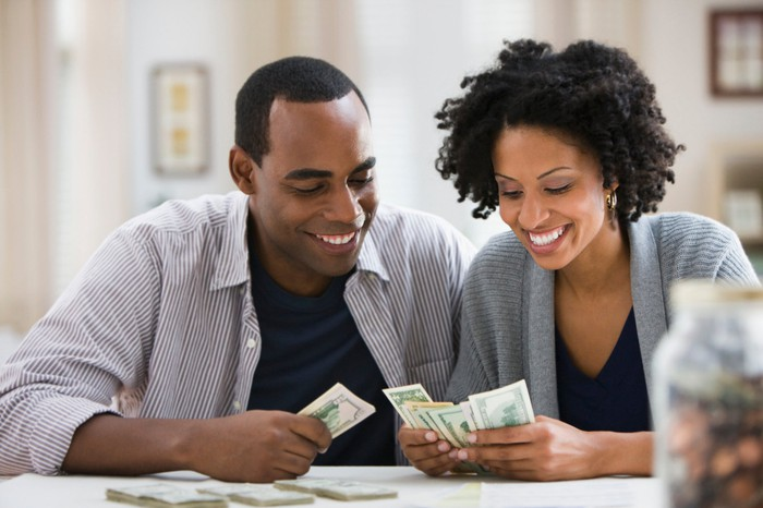 A man and a woman smile while sitting at a table in a home counting cash they are holding in their hands and on the table