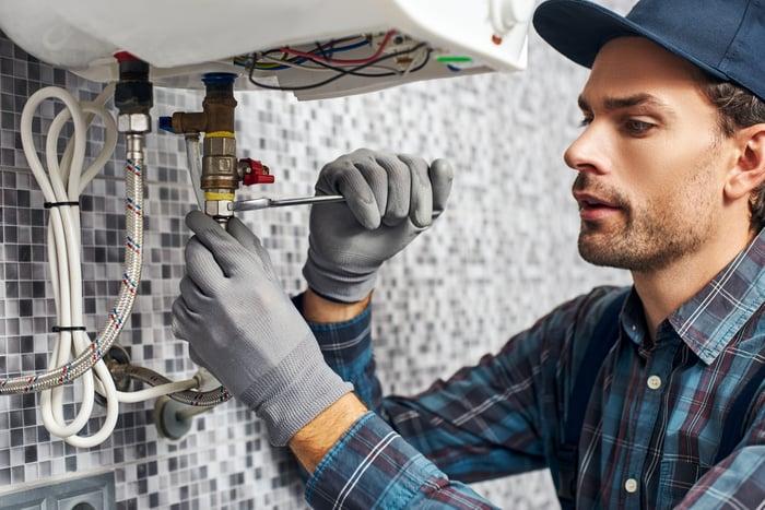 A plumber tightens a nut under a sink.