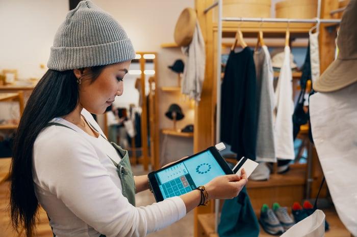 Employé de magasin de détail prenant un paiement par carte sur une tablette.