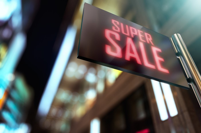 A lit LED sign in front of a store that reads, Super Sale.