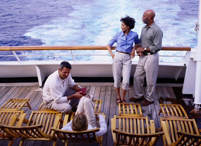 People on the deck of a cruise ship that's underway.
