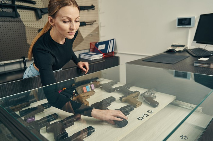 A gun store employee reaches into a glass display case full of firearms.