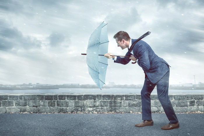 Person holding an umbrella up against a storm wind.