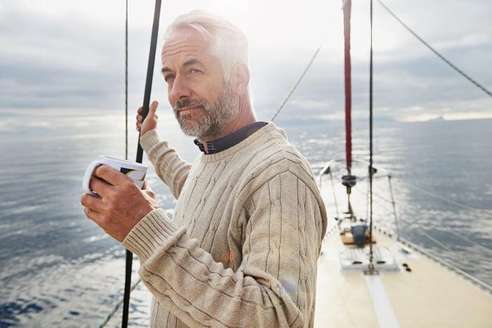 Senior person on sailboat holding mug.