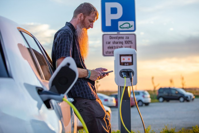 Driver of electric vehicle checking phone while at charging station