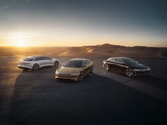 Three parked Lucid Air sedans overlooking a sunset.