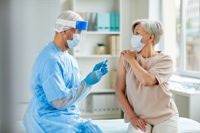 A masked, gloved, and shielded healthcare professional holding a syringe with needle and vaccine vial near the arm of a masked patient.
