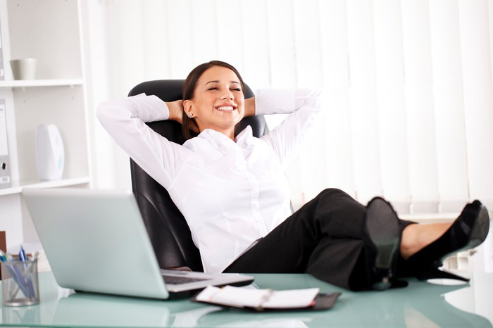 A smiling person with eyes closed leaning back in a chair with feet on desk next to a laptop.