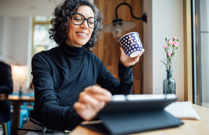 A smiling person holding a coffee cup and looking at a touchscreen tablet.