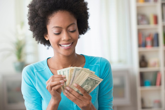 An investor smiles as she counts a handful of bills.