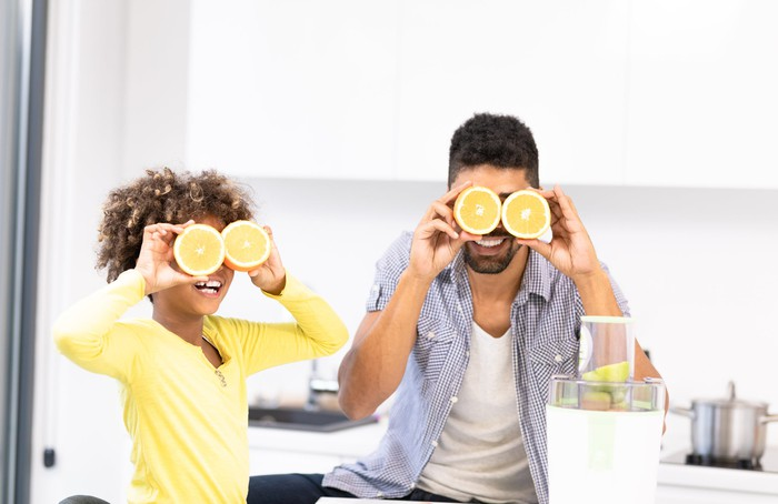 A man and a child in a kitchen holding cut lemons over their eyes.