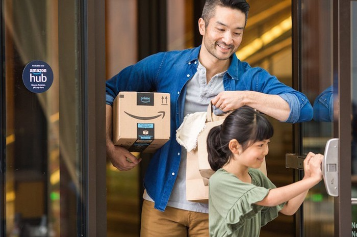 A father carrying an Amazon package under his arm while his young daughter holds open a door.