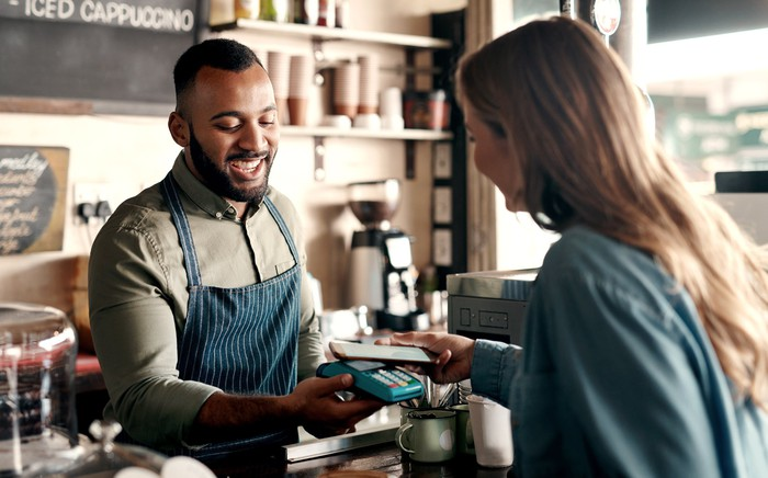 Woman uses phone to pay at coffee shop.