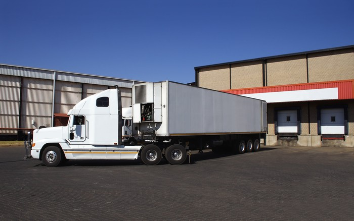 A white semitruck backed up to a loading bay at a warehouse.