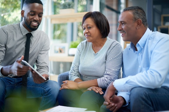 Un conseiller montre des informations sur une tablette à deux adultes.