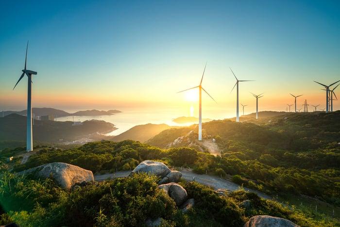 Wind turbines on hilly terrain.