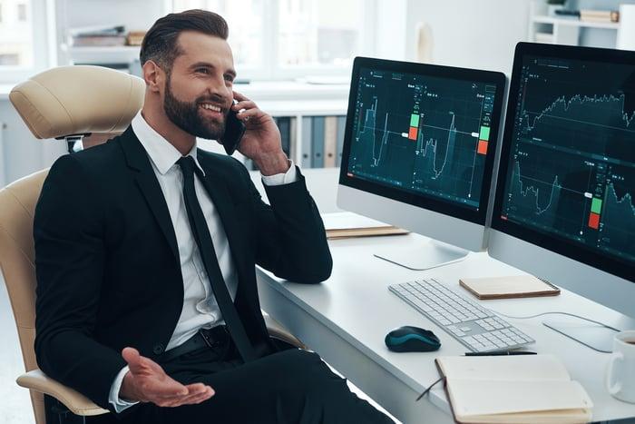 Investisseur parlant au téléphone, tandis que des graphiques financiers sont affichés sur les ordinateurs de son bureau.