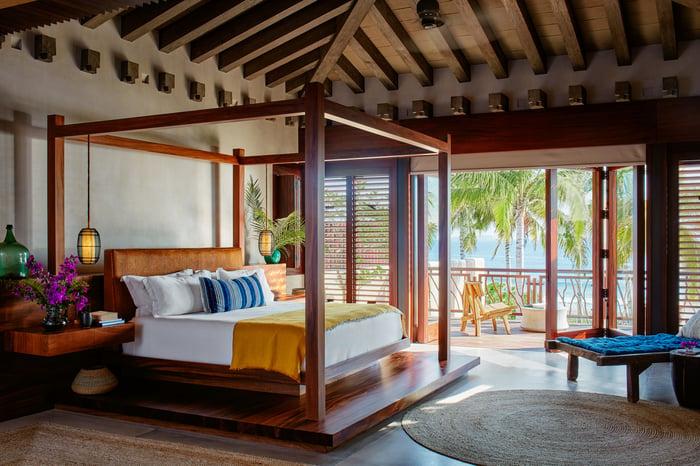 Chambre sur le thème du bois qui s'ouvre sur une véranda avec vue sur les palmiers au bord de l'océan.