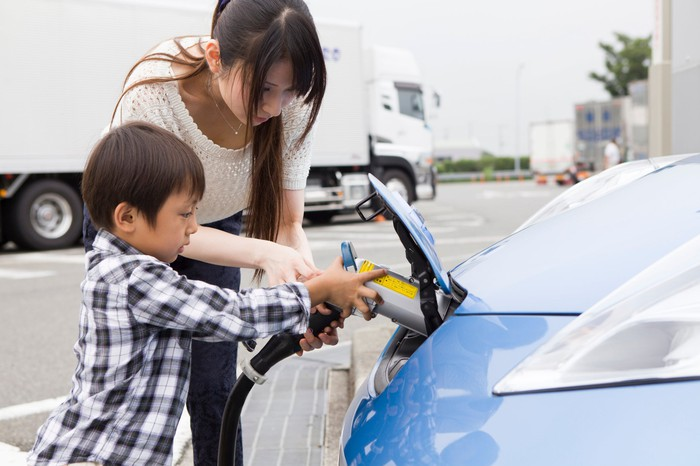 Adult and child charging electric vehicle at station.