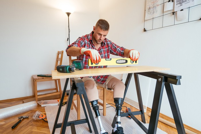 Person with prosthetic legs measuring boards on a sawhorse.