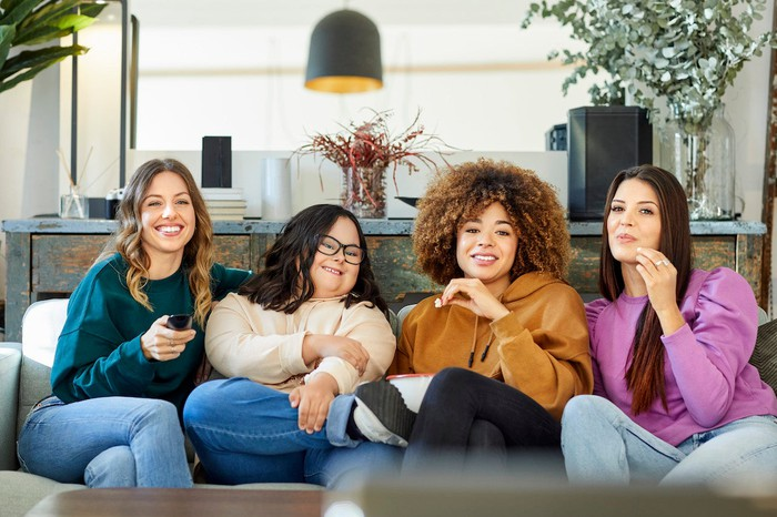 Four friends enjoy a TV show together on the couch.
