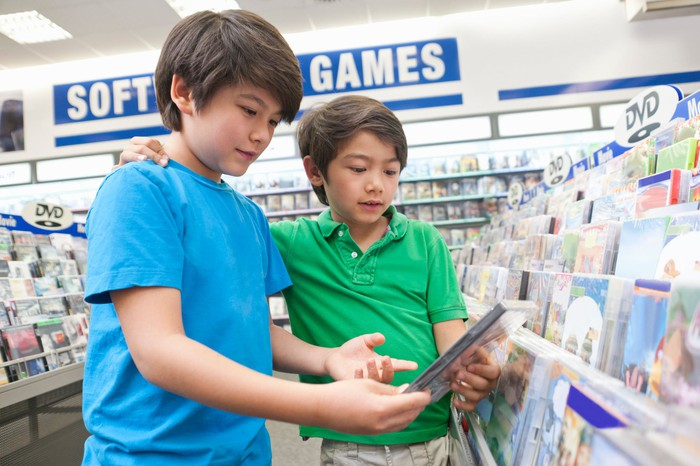 Two kids shopping for video games in a bricks-and-mortar store.