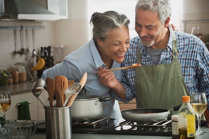 Two people standing over stove